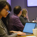 a student works diligently at their laptop during presentation