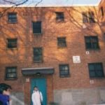 Two children standing in front of public housing building